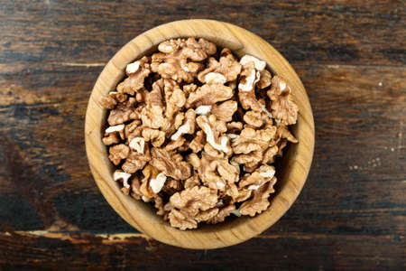 unshelled walnuts in a plate on a wooden background. view from above. place for text