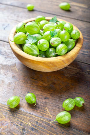 Fresh green gooseberries in a wooden plate on a wooden background. summer vitamin harvest