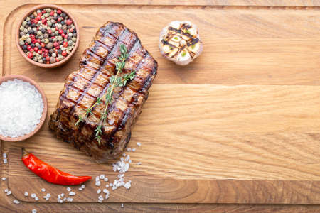 grilled steak grilled on a wooden background, with spices. grill strips visible on steak Фото со стока