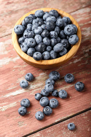 organic blueberries in a wooden plate and sprinkled on a table, on a wooden background. place for text