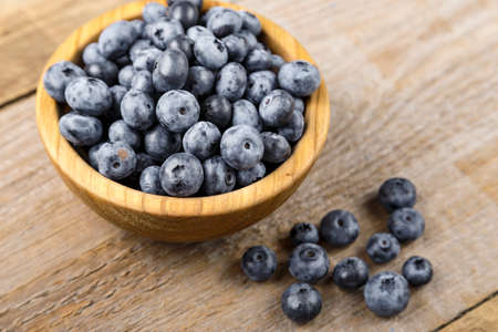 ripe blueberries in a wooden plate on a brown wooden background. clearly visible texture of berries Фото со стока