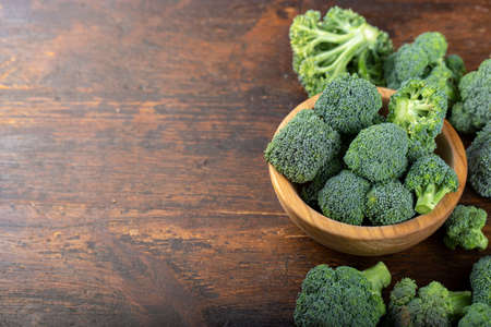 Fresh broccoli with in bowl on wooden table close up. Fiber-rich food.