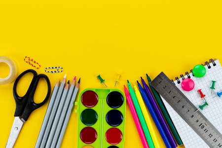 School accessories on a yellow background. View from above Фото со стока