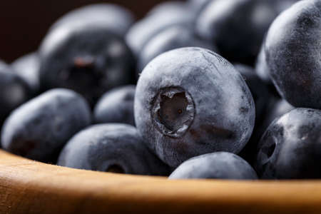 ripe blueberries in a wooden plate. side view. close-up. clearly visible texture of berries
