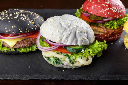 burgers in colorful buns. assortment of meat burgers with vegetables