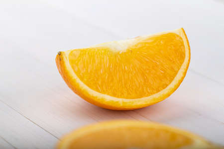 Sliced orange on a white wooden background.