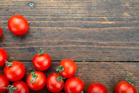 ripe tomatoes are scattered on a brown wooden table. farmer organic crop. place for text Фото со стока