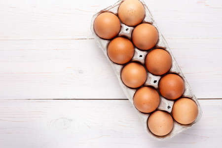 farm red chicken eggs in a cardboard tray on a wooden background. place for text