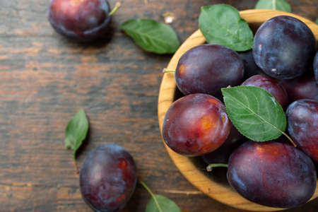 Fresh plums in a wooden bowl. Harvesting. Delicious fruits. Фото со стока