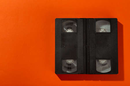 Videotape without a cover on an orange background. Top view. 版權商用圖片