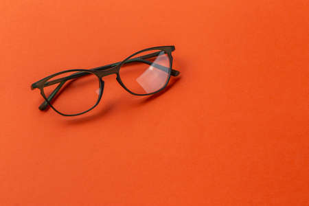 Glasses for sight in olive frames on an orange background. Fashion accessories. 免版税图像