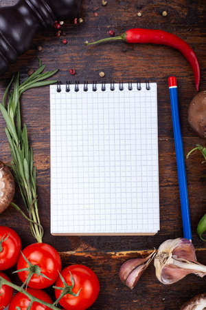 notebook for recipe and vegetables on a light wooden background. Space for text. 免版税图像