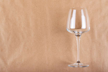 Empty wine glass on crumpled paper background. Space for text. 免版税图像