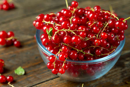 Fresh red currant berries in plate on wood background.