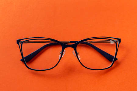 Glasses for vision in blue frames on an orange background. Fashion accessories.
