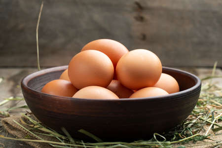 Fresh chicken eggs in a clay bowl on the hay. Rural scene.