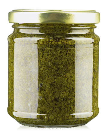Homemade basil pesto sauce in glass jar on white background. File contains clipping path. 免版税图像