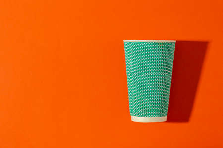 Paper cup for coffee on an orange background. Coffee to go.