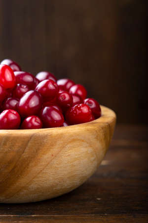 Dogwood berries in a wooden bowl on a wooden background.