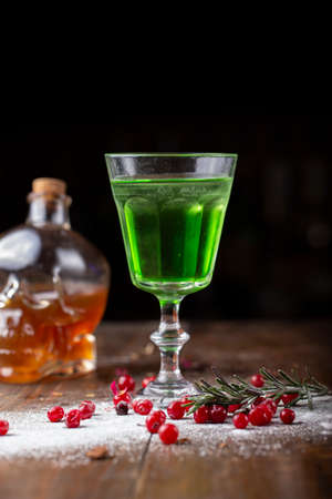 green cocktail on the basis of absinthe in a stylish vintage glass on a brown wooden background.