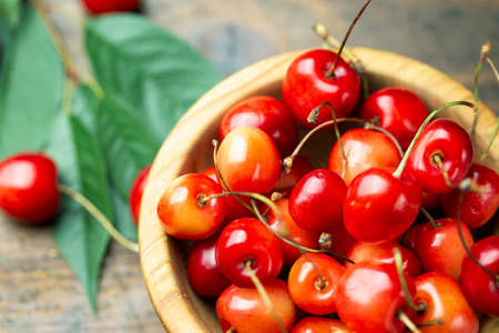 Fresh sweet cherries with leaves in a wooden plate on a wooden background. Banco de Imagens