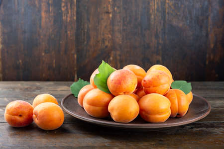 Ripe apricots and leaves in a clay bowl on a wooden background. Banco de Imagens