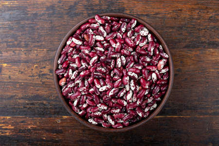 Red and white beans in a bowl on a wooden background. Top view.