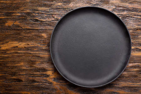 Empty cast iron frying pan on wooden culinary background. Space for text. Top view.