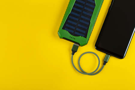 Smartphone Charging with Power Bank on Yellow Background Top View Banco de Imagens