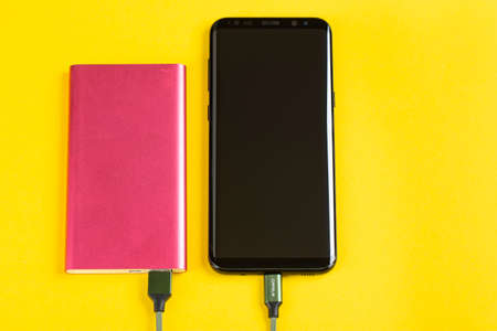 Smartphone Charging with Pink Power Bank on Yellow Background Top View Banco de Imagens