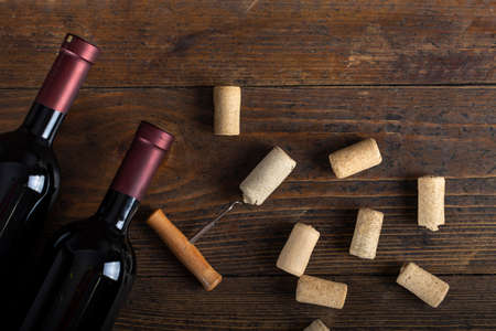 Two bottles of wine, corkscrew and corks. Space for text. Top view.