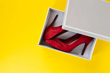New women's red suede shoes in a box on a yellow background. Top view. Banco de Imagens