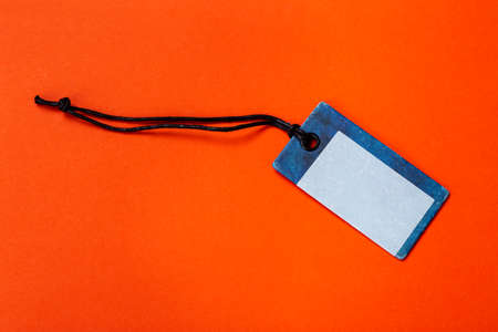 Blank tag tied for hang on product for show price or discount isolate on orange background.