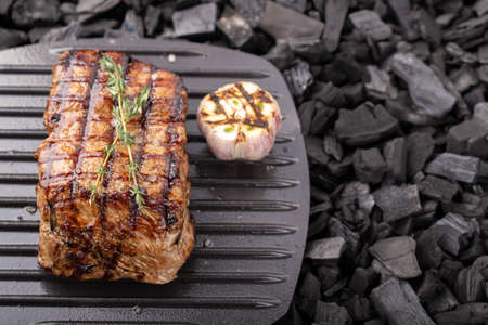 Grilled beef steaks with spices grilled. Coals in the background.