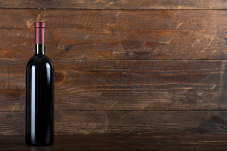 Wine bottle on wooden background. Space for text. Banco de Imagens