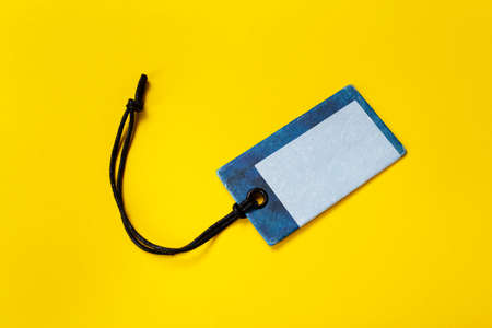 Blank tag tied for hang on product for show price or discount isolate on yellow background.
