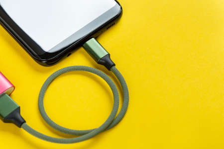 Charging a mobile phone on a yellow background. Banco de Imagens