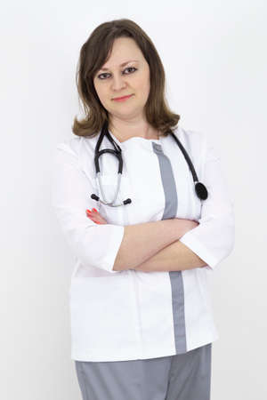 adult female doctor with a stethoscope against a white wall. experienced doctor who inspires confidence Banco de Imagens