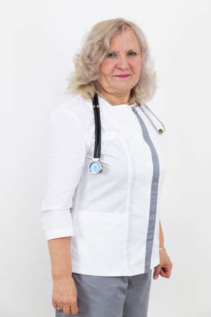 Adult female doctor with a stethoscope against a white wall. experienced doctor who inspires confidence. Banco de Imagens