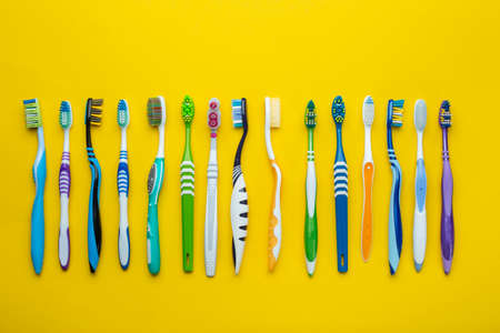 Toothbrushes on yellow background. Hygiene of the oral cavity. Top view.