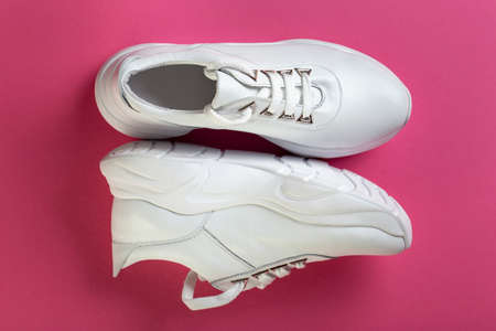 Pair of new white sneakers on pink background. Comfortable casual shoes 写真素材