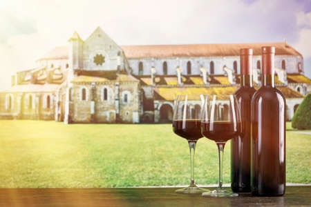 Two bottles of wine and two glasses against the background of an ancient monastery. With space for text. 写真素材