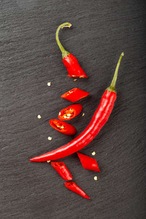 Red whole and chopped chili peppers on a black slate board. Spicy food concept. Space for text. Top view.