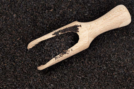 Dry black tea leaves on which there is a wooden scoop for a set of bulk products.