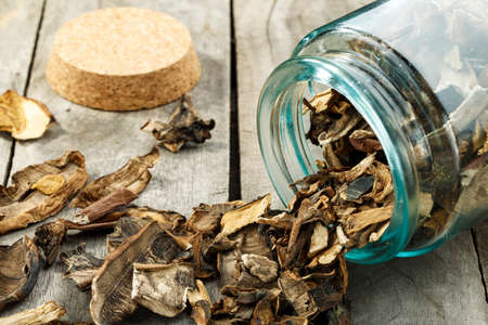 Dried mushrooms in a glass jar on a wooden table. Space for text. Closeup.