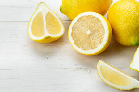 Ripe lemons on a white wooden table.