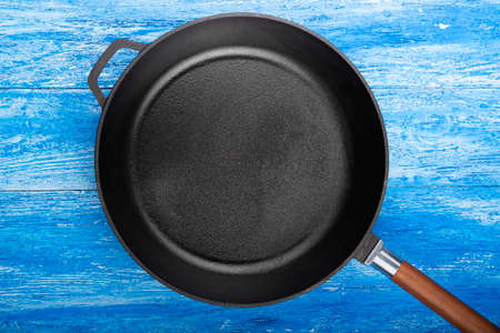 Empty cast iron pan on wooden culinary background, space for text. Top view.