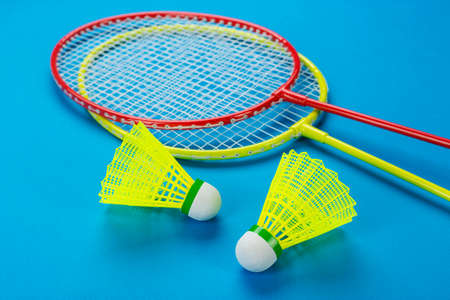 Two shuttlecock and badminton rackets on blue background. Active recreation and sports concept. Space for text.