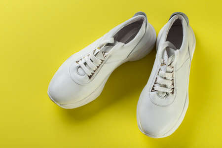 Pair of new white sneakers on yellow background. Comfortable casual shoes