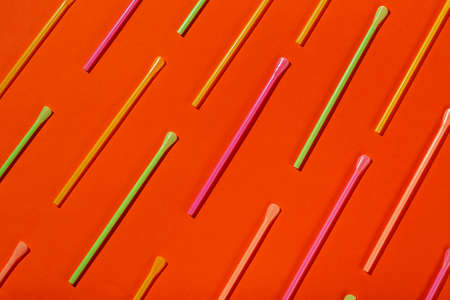 Patterns with сolored tubules for juice and cocktails on orange background. Space for text. Top view.